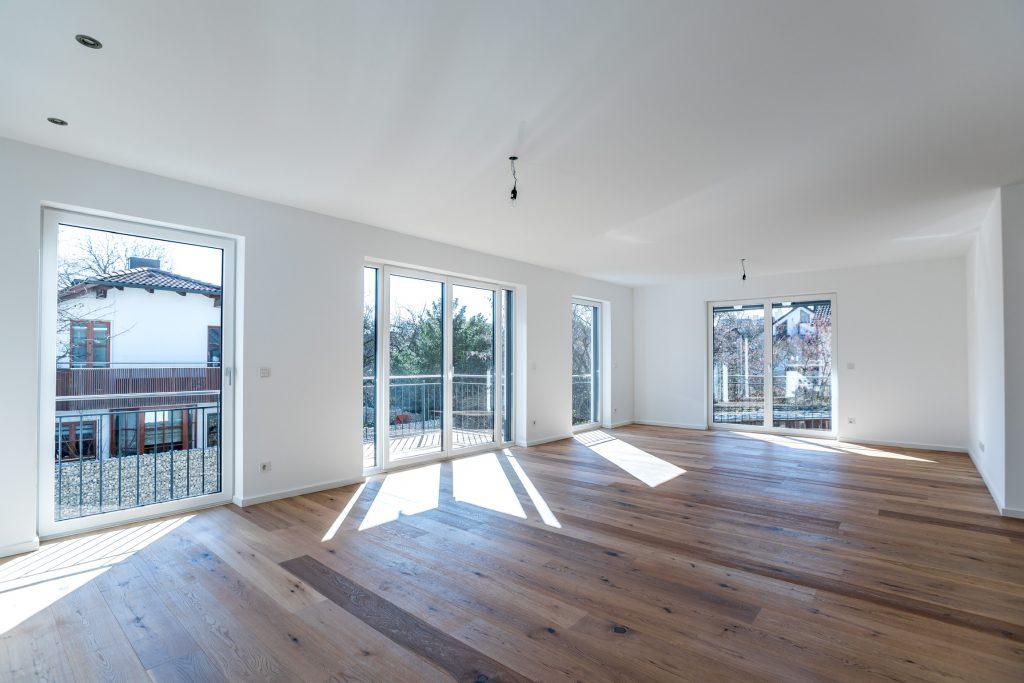 Mehrfamilienhaus München Trudering großes Wohnzimmer mit Balkon im ersten Stock.