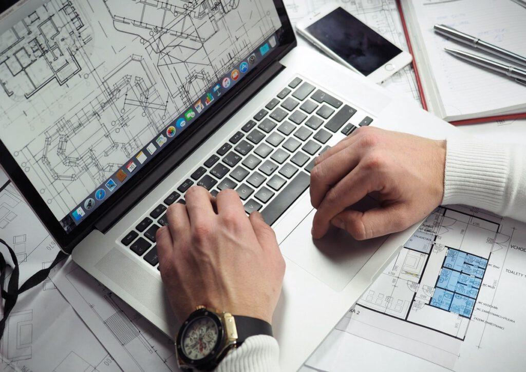 Schreibtisch mit Planungsunterlagen und einem Laptop mit einem geöffneten Bauplan.